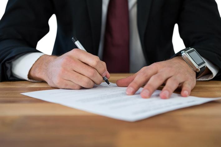 Nach erfolgreichem Neubauvertrieb unterschreibt ein Interessent im Anzug den Kaufvertrag.