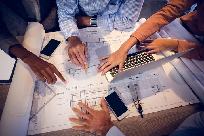 Vier Beteiligte eines Bauprojekts sehen sich Baupläne an, um einen Neubauvertrieb in Dormagen, Neuss oder Langenfeld zu planen.