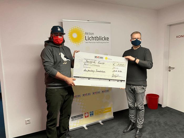 Patrick Kuhlmann überreicht einen Spendenscheck an die Aktion Lichtblicke.