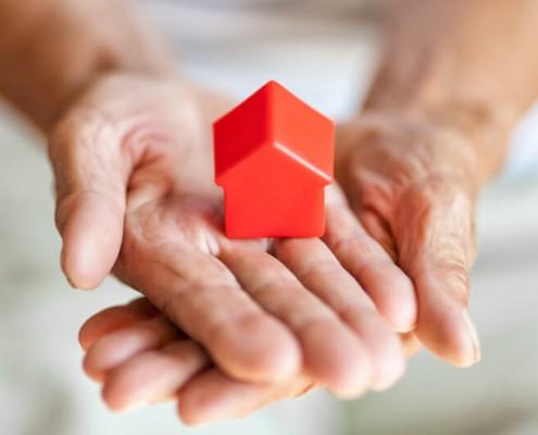 Symbol für lebenslanges Wohnrecht, alte Händen halten ein rotes Modell eines Hauses